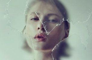 Vrouw achter gebroken glas als symbool voor de kenmerken van negatieve mensen