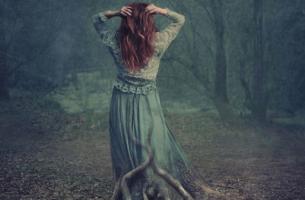 Vrouw die in een bos staat, geworteld aan de grond, en last heeft van een verborgen depressie