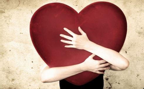 Vrouw houdt krampachtig een hart vast als voorbeeld voor ongezonde emotionele afhankelijkheid