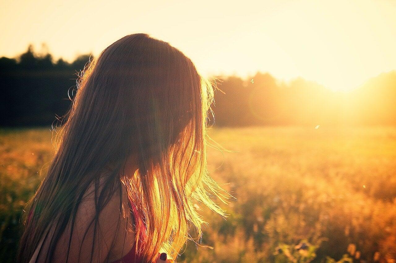 Vrouw in weiland ervaart innerlijk geluk