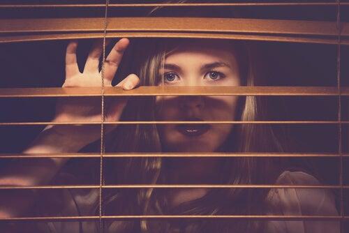 Vrouw met aangeleerde hulpeloosheid kijkt door de luxaflex