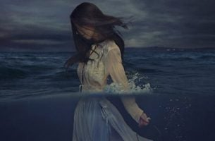 Vrouw loopt door het water, als symbool voor de veerkracht van slachtoffers