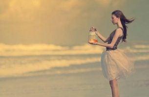 Meisje laat goudvis vrij in oceaan, als symbool voor je leven veranderen