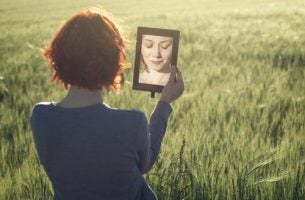 Vrouw die in de spiegel kijkt en weinig zelfliefde heeft