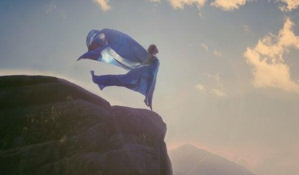 Vrouw die op een hoge rots staat met haar armen wijdgespreid