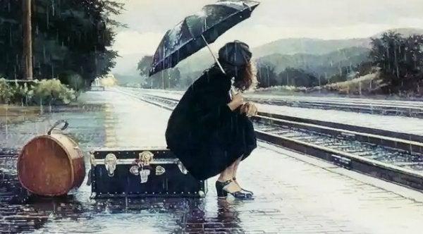 Vrouw wacht met al haar eigendommen op de trein