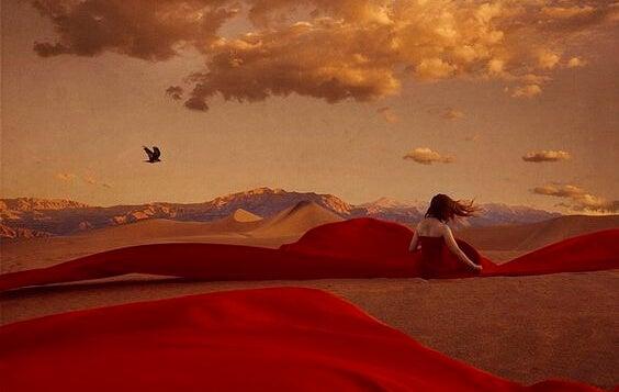 Vrouw met een rode jurk aan die in haar eentje in de woestijn zit om de emotionele wond op haar ziel te genezen