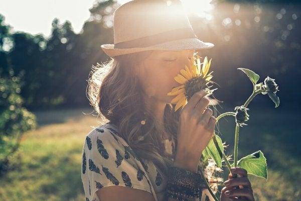 Vrouw die aan een zonnebloem ruikt, want positief denken draagt bij aan geluk