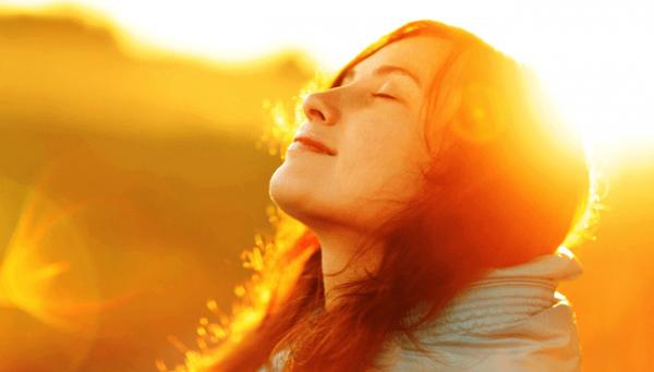 Vrouw die geniet van de zon op haar gezicht