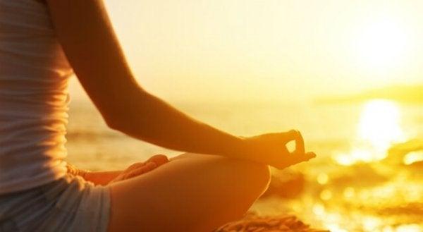 Vrouw die mediteert op het strand