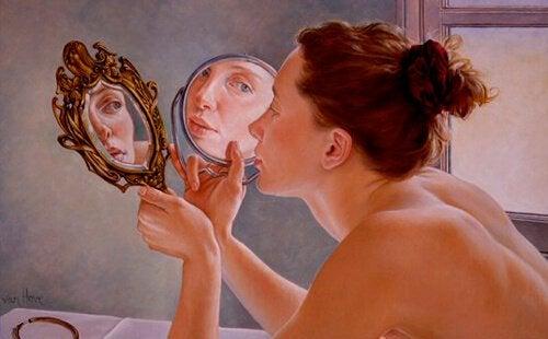 Vrouw die naar zichzelf kijkt in de spiegel