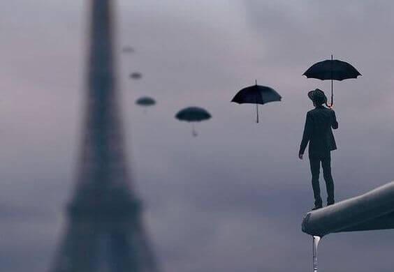 Man die kijkt naar een rij paraplu's die naar de Eiffeltoren reiken