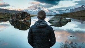 Man die voor een meer en een berg staat