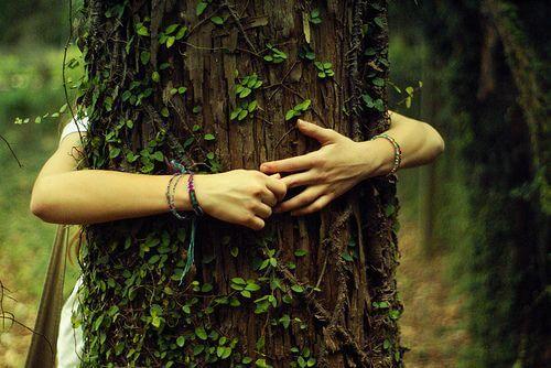Vrouw die een boom omhelst vanwege de kracht van dankbaarheid