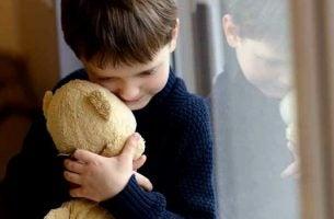 Jongetje uit een disfunctioneel gezin dat stevig zijn knuffelbeer vasthoudt