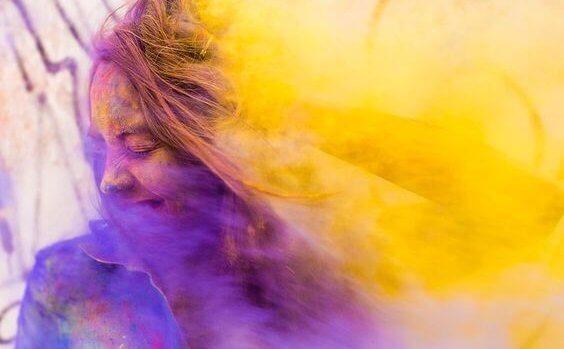 Meisje dat lacht in een paars met gele wolk van rook