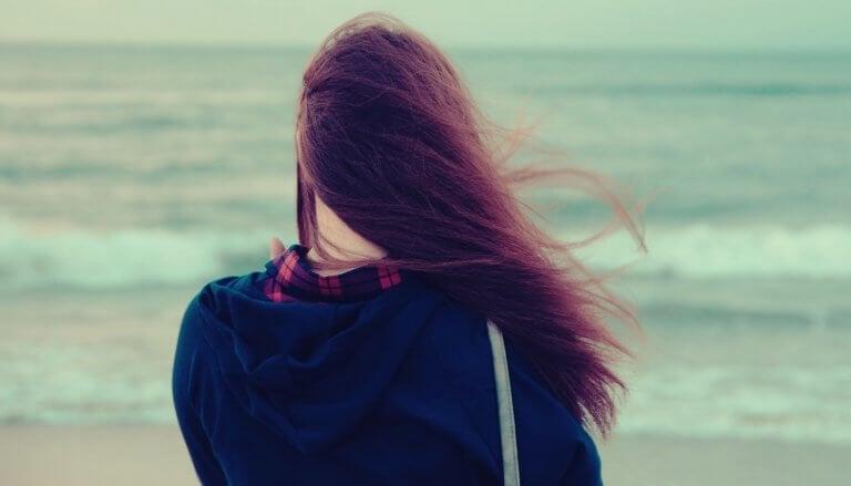 Meisje dat uitkijkt over de zee