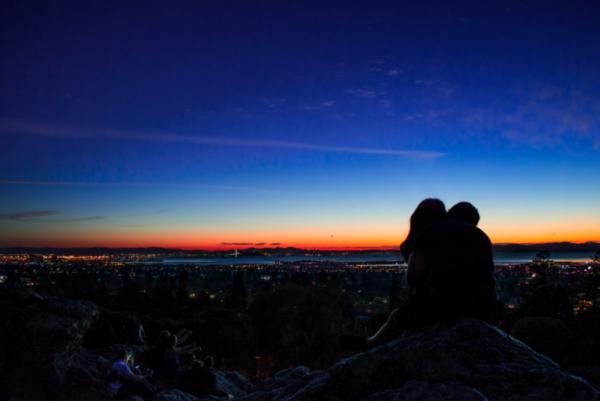Man en vrouw kijken naar de zonsondergang