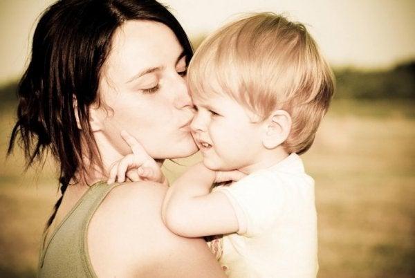 Moeder die haar zoontje een kusje geeft