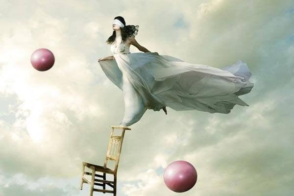 Vrouw die geblinddoekt balanceert op de leuning van een stoel