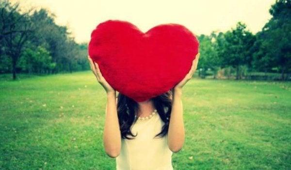 Meisje dat haar gezicht verbergt achter een groot hart, want gezonde stelletjes voelen liefde voor elkaar