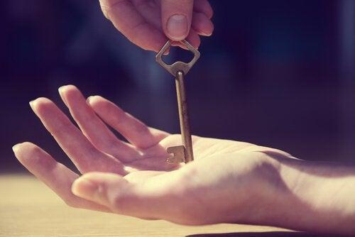 Vrouw die een sleutel op haar hand probeert te balanceren