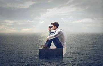 Man die op een steen midden in de oceaan door een verrekijker kijkt, want we moeten dingen doen die onmogelijk lijken