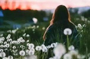 Meisje in bloemenveld dat zegt: ik hou niet meer van je