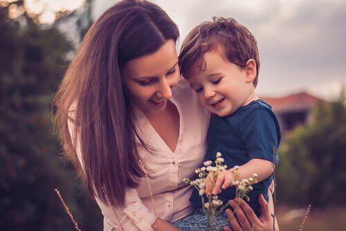 Moeder die met haar zoontje naar bloemen kijkt, want ze is geen slechte moeder
