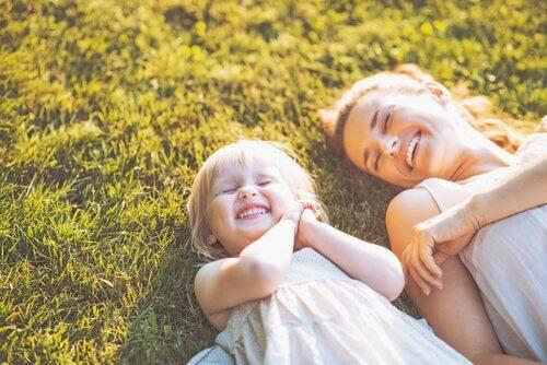 Moeder die met haar dochter ligt te lachen in het gras, want ze is geen slechte moeder