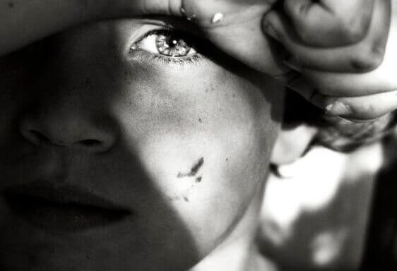 Jongen met pijn in zijn ogen omdat hij uit een disfunctioneel gezin komt