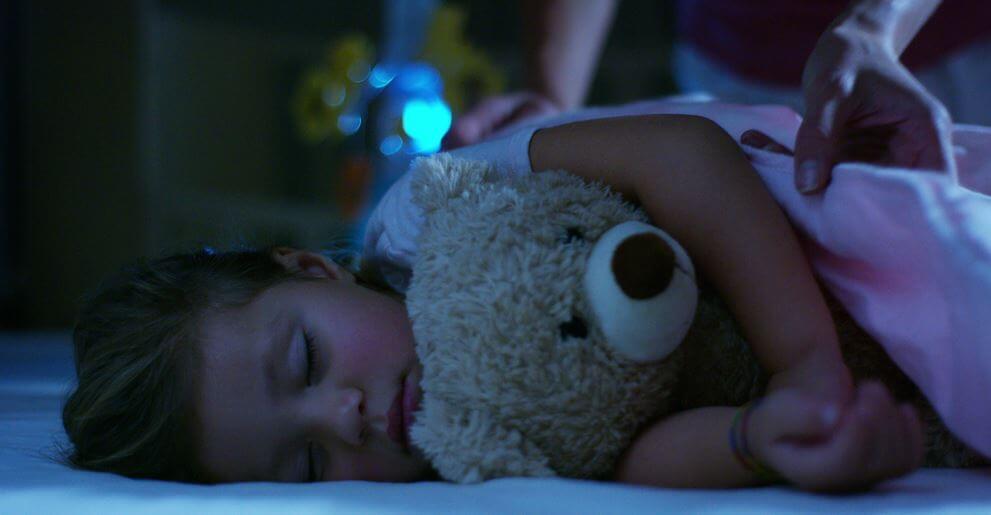 Meisje dat ligt te dromen met haar teddybeer in haar armen