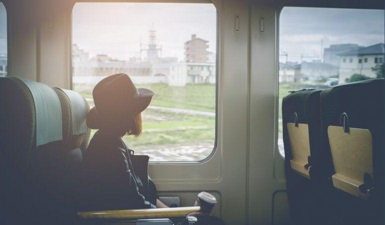 Meisje dat in de trein zit en uit het raam kijkt en nadenkt over het verbreken van een relatie