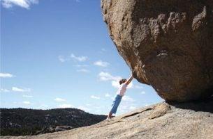 Jongetje dat zogenaamd een grote steen omhoog duwt, als voorbeeld van dingen doen die onmogelijk lijken