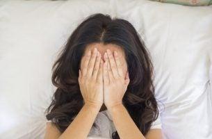 Vrouw die met haar handen op haar gezicht in bed ligt, want ze kan geen orgasme krijgen