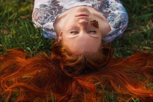 Vrouw ligt in het gras en weet: leven in het heden is belangrijk
