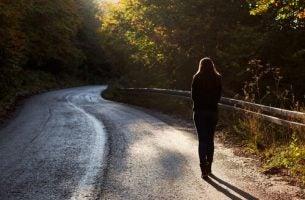Vrouw die alleen op een weg loopt en vaarwel zegt