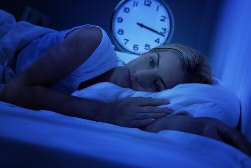 Vrouw die 's nachts wakker ligt omdat ze naar witte ruis luistert