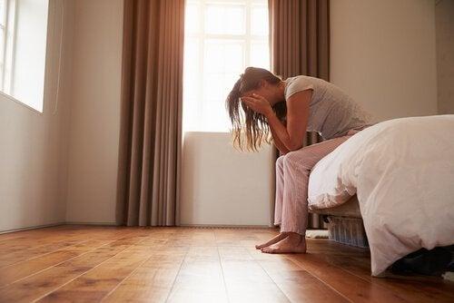 Vrouw die huilend op haar bed zit omdat ze last heeft van vaginisme