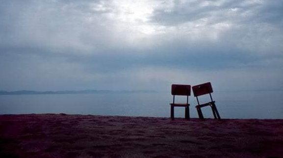 Twee eenzame stoelen op een strand
