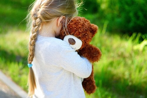 Meisje dat haar teddybeer knuffelt