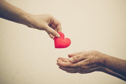Vrouw geeft hart aan oudere vrouw als voorbeeld van compassie