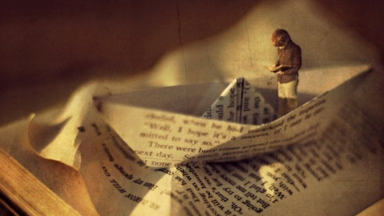 Klein mannetje die staat te lezen in een boek