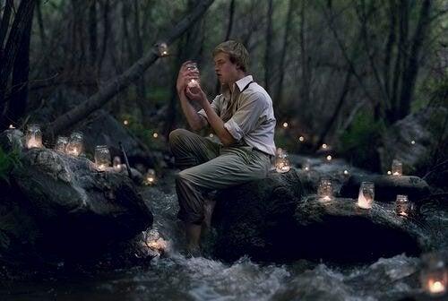 Man die in een bos zit omringd door kaarsjes, want het leven bevat meer fantasieën dan werkelijkheden
