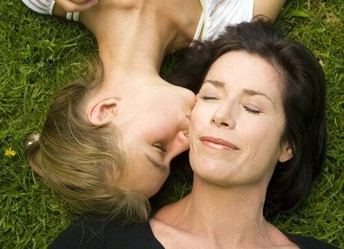 Dochter die haar moeder een kus op haar wang geeft