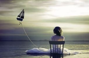 Vrouw die in haar eentje aan de zee zit en lijdt aan chronische eenzaamheid