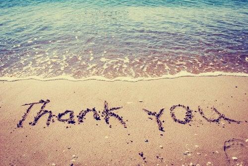 De woorden 'thank you' geschreven in het zand
