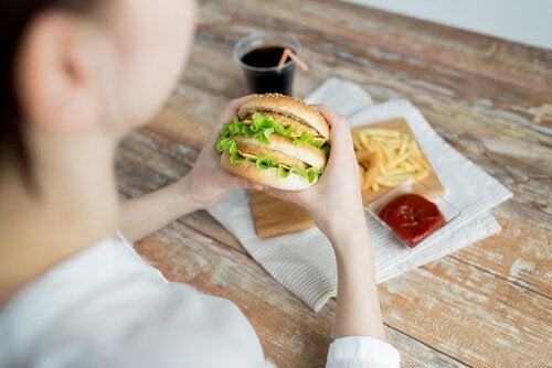 Vrouw met emotionele honger eet fastfood