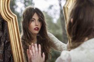 Vrouw kijkt naar haar reflectie in de spiegel