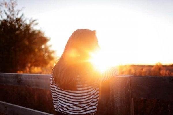 Meisje kijkt uit over weiland bij zonsondergang